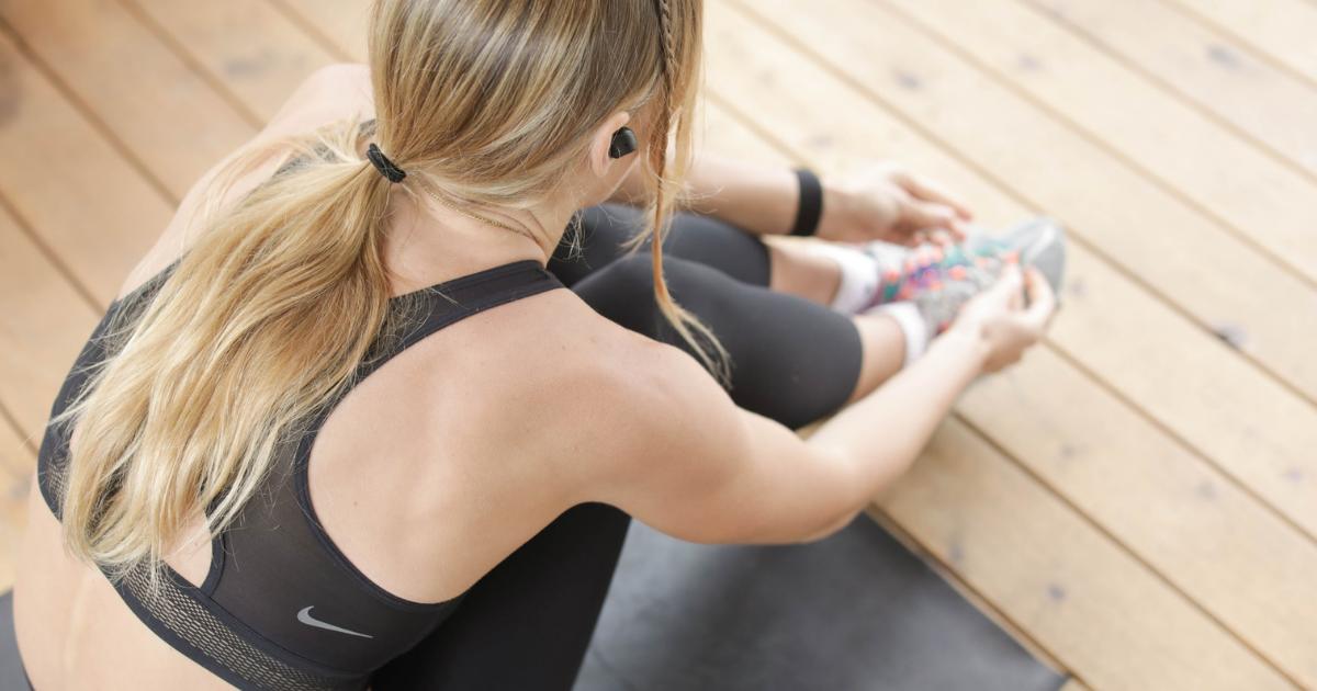 Foto di una donna bionda di spalle, vestita da fitness, seduta a terra mentre si allaccia le scarpe.