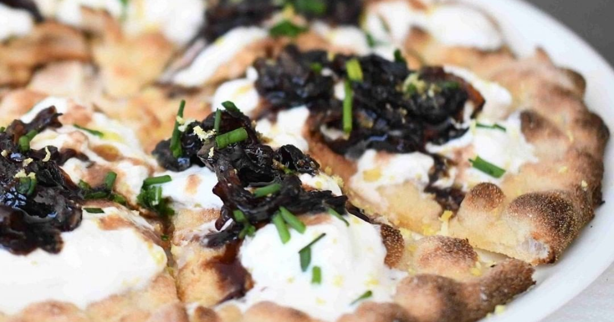 Dettaglio di una pizza condita con formaggio e verdure